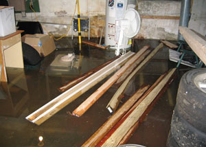 A severely flooding basement in Bryant, with lumber and personal items floating in a foot of water